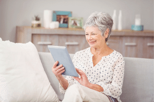 Senior woman smiling while reading E-reader on couch