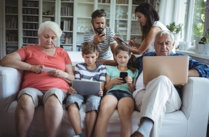 Communication Tactics to Use with Your Aging Parent – Family on couch all using digital devices instead of communicating with each other