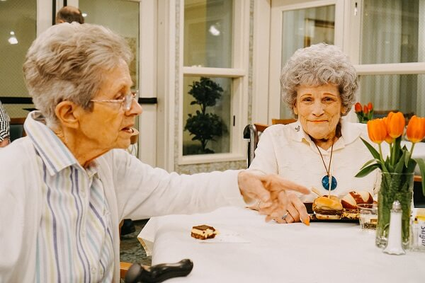 Two elderly women eat at a table while one smiles at the camera in Federal Way, Washington