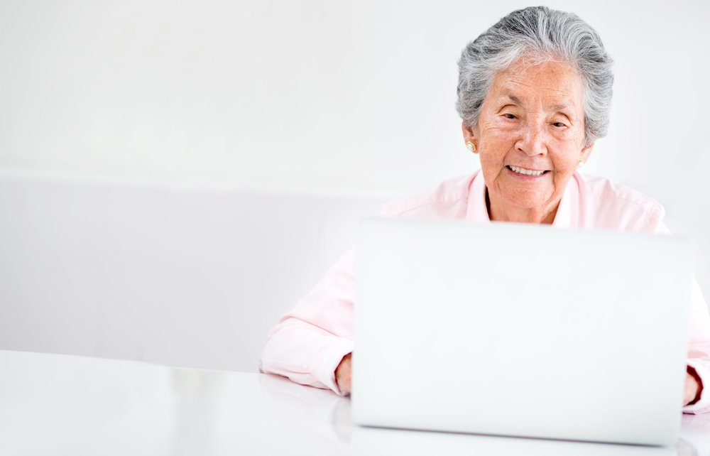Portrait of an old woman using a computer