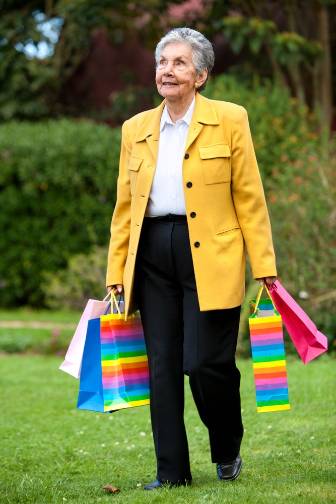 Senior woman walking outdoors with shopping bags